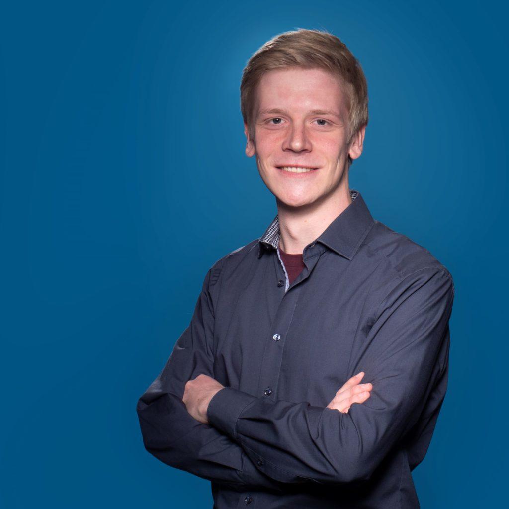 Porträt von Thomas Stephan vor blauem Hintergrund