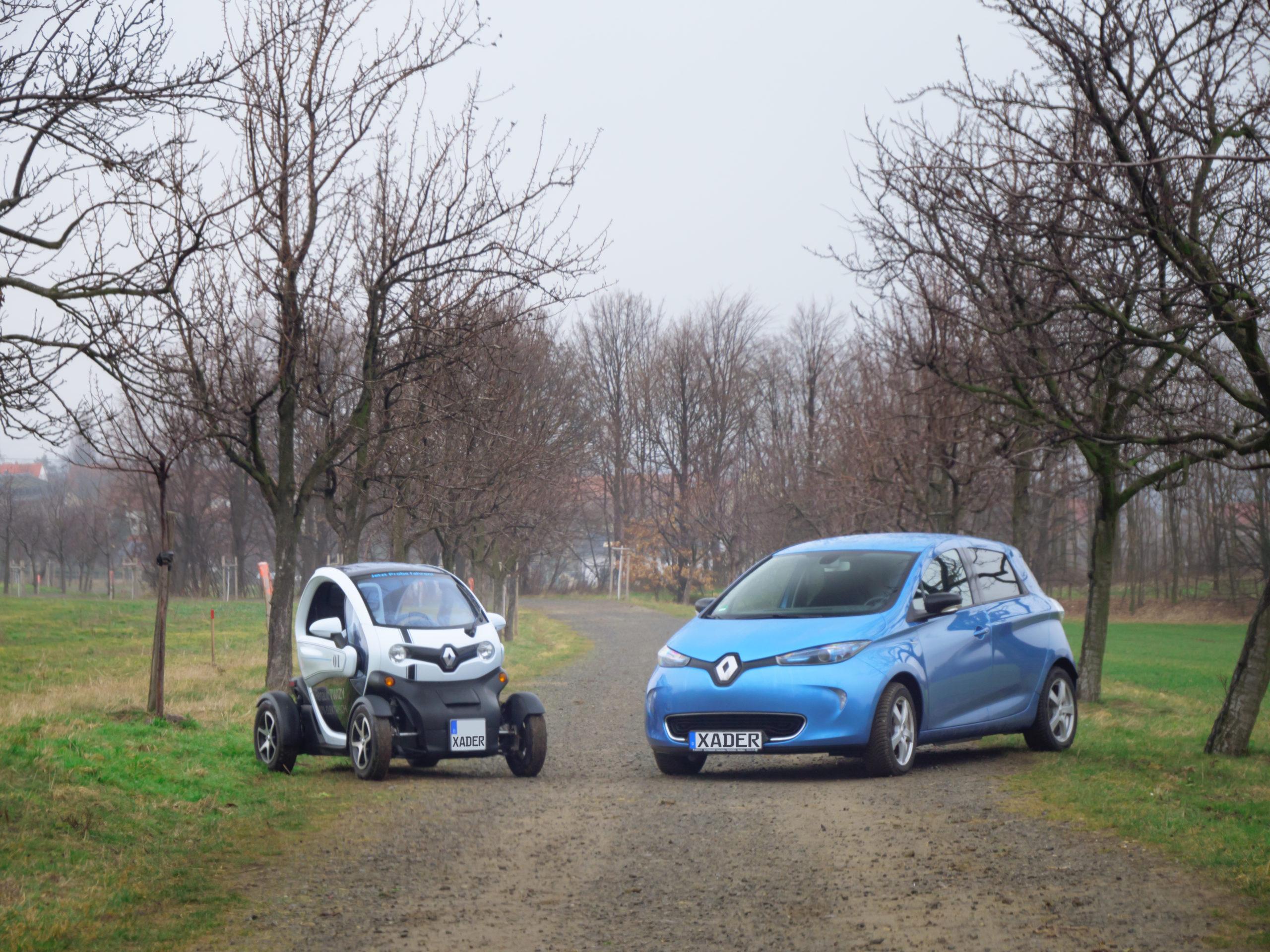 Renault Twizy und blauer Zoe stehen auf Feldweg-Allee nebeinander